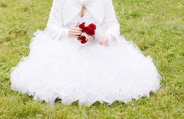 Bride in white dress sitting on green grass