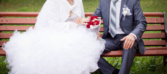 Bride and groom sitting on a bench in a park