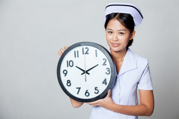 Young Asian nurse with a clock