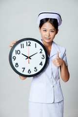Asian young nurse show thumbs up with a clock