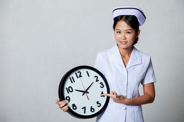 Young Asian nurse point to a clock