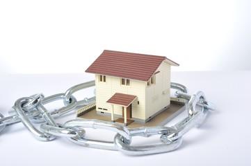 鎖を巻かれた住宅模型