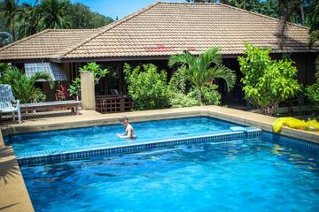 boy swims into blue swimming pool in resort. Koh Samui