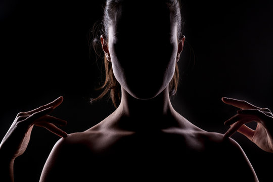 woman with the face in the shadow touches her shoulders