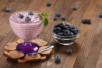 yogurt with blueberries in a glass bowl and blueberries in a gla