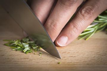 Cocinero picando romero a cuchillo en la mesa de la cocina