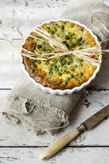 vegetables french quiche with peas on baking dish with knife