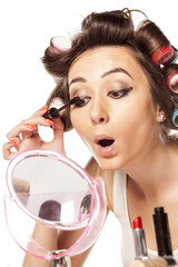 housewife with curlers and apply mascara