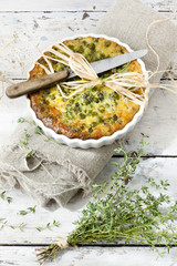 vegetables quiche with peas on baking dish with thyme bouquet