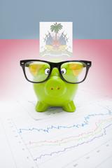 Piggy bank with flag on background - Haiti