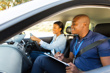Fototapete - african driving instructor and learner driver