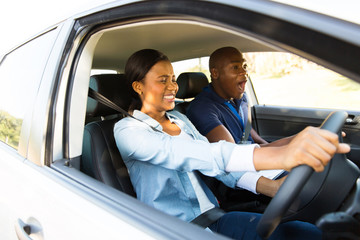Fototapete - african girl taking driving lessons for the first time