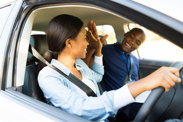 Fototapete - young african learner driver and driving instructor high five