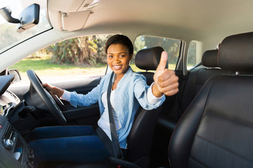 Fototapete - young african female driver giving thumb up