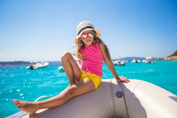Cute little girl enjoying sailing on boat in the open sea
