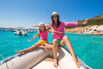 Young mother with her adorable daughter enjoy vacation on a boat