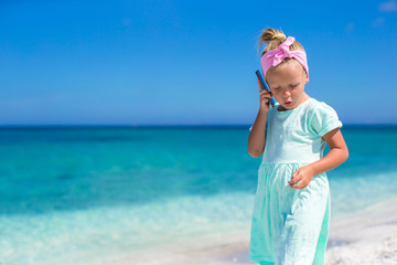 Little adorable girl talking at phone during beach vacation