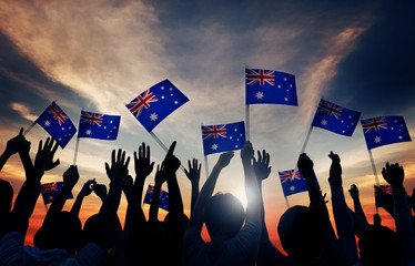 Group of People Waving Australian Flags in Back Lit