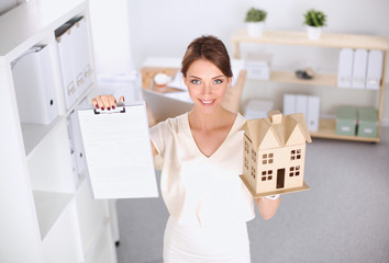 Portrait of female architect holding a little house, standing in