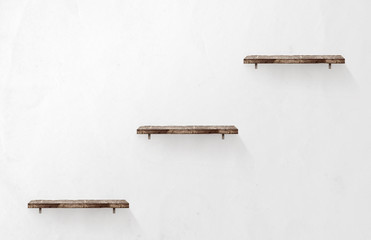 Three empty wooden shelves on the wall