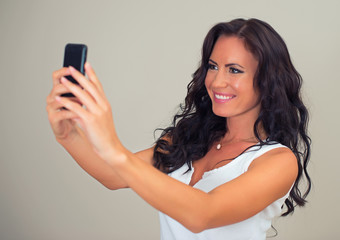 Attractive brunette taking selfie with cellphone.
