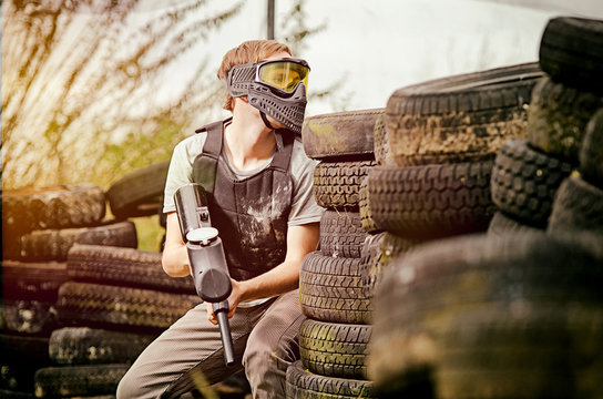 Paintball player standing  behind cover