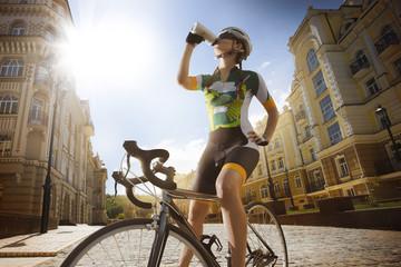 Cyclist is drinking water from the sport bottle