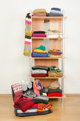 Wardrobe with winter clothes arranged on shelf and full luggage.