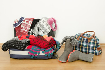Luggage and bag full with winter clothes and accessories.