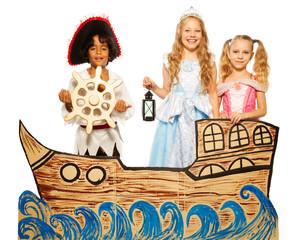 Three kids, pirate and princess on cardboard ship