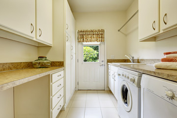 Bright laundry room with white cabinets