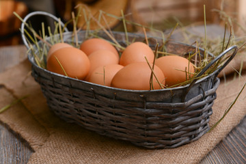 Eggs in wicker basket on table close-up