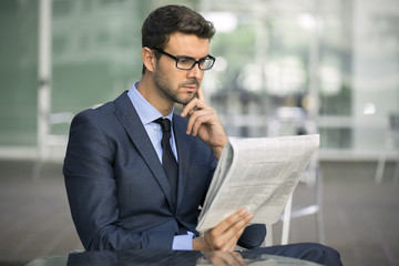Focused businessman with glasses reading newspaper
