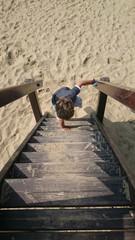 Junge an Holztreppe Strandspielplatz