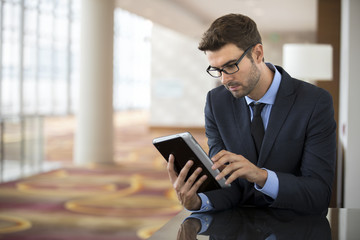 Focused businessman with glasses using tablet at the hotel lobby