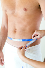 Man with a helthy body measuring his stomach. Diet concept.