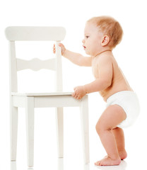 happy baby  playing with white chair