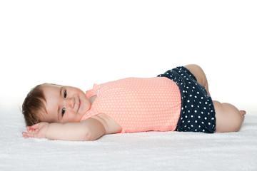 Smiling infant girl on the white towel
