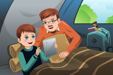 Father and son reading a tablet PC in a camping tent