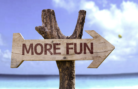 More Fun wooden sign with a beach on background