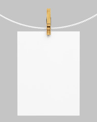 white paper hanging on rope with clothespin