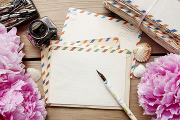 Handwritten letters and bouquet of pink peonies