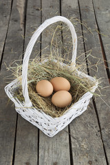 Three eggs on hay in white basket on wooden background