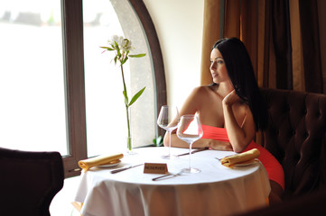 Beautiful brunette woman waiting at the table in restaurant