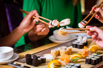 Foto auf Acrylglas Sushi bar Junge Leute essen Sushi in Asia Restaurant