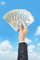 Hand giving money -  United States dollar (USD) bills