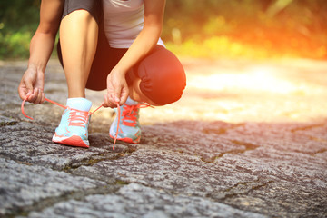 woman runner tying shoelace on stone trail