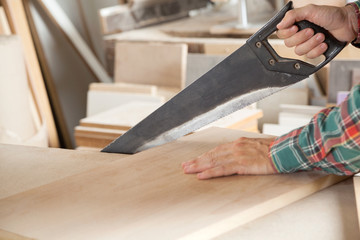 Carpenter Cutting Wooden Plank With Handsaw