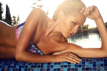 beautiful girl  in bikini posing beside a swimming pool