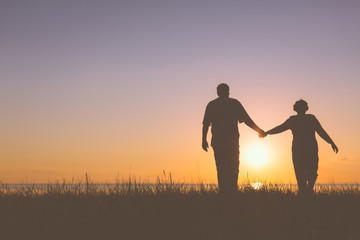 Senior couple holding hands silhouettes